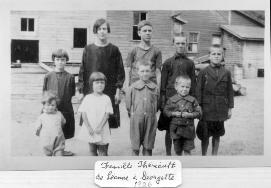 Joachim and Annie Theriault's children in 1926: backrow: Annette, Leanne, Denis, Thaddée, Theodule. Front row: Georgette, Rita, Felix, George. Posing with the old Baker-Brook saw/flour mill in the background. The mill was water-driven. The date of this photo is given by Georgette Theriault Cyr, the youngest in the photo. She was two years old at the time of this photo. Georgette noted that she is the only child in the family with curly hair and it was not often that her elder siblings would take the time to comb her hair.